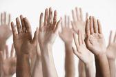 Men and women raising hands — Stock Photo