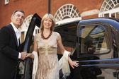 Couple exiting London taxi — Stock Photo