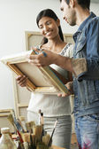 Couple looking at canvases in artist studio — Stock Photo