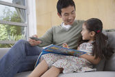 Daughter with picture book with father — Foto de Stock