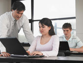 Teacher with students in computer classroom — Stock Photo