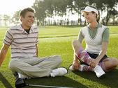 Golfers sitting on court smiling — Stock Photo