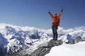 Mountain climber with arms raised — Stock Photo