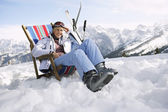 Skier sitting on deckchair — Stock Photo