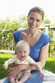 Mother and son sitting on rug in garden — Stock Photo