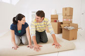 Couple unrolling carpet in new home — Stock Photo