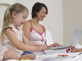 Mother and daughter drawing and using laptop — Stock Photo