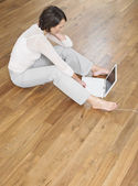 Woman sat on floor using laptop — Stock Photo