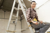 Interior decorator sitting on ladder — Stock Photo