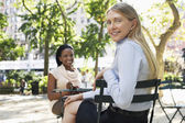 Female colleagues sitting at street cafe — Stock Photo