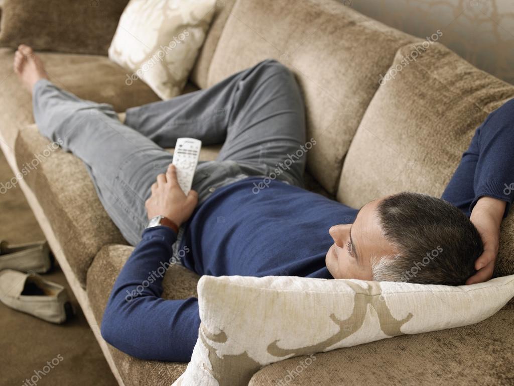 homme regarder la t l vision sur le canap photo 33848195. Black Bedroom Furniture Sets. Home Design Ideas