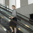 Woman standing on escalator — Stock Photo #33850901