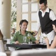 Waiter pouring wine for couple at restaurant — Stock Photo