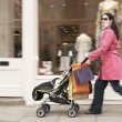 Mother pushing stroller by shop — Stock Photo #33850457