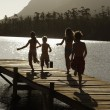 Children running down dock by lake — Stock Photo