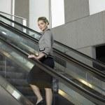 Woman standing on escalator — Stock Photo #33850901