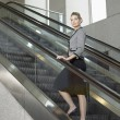 Woman standing on escalator — Stock Photo #33851055