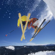 Stock Photo: Skiers launching off snow bank