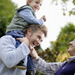 Boy riding on father's shoulders — Stock Photo #33851159