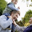 Boy riding on father's shoulders — Stock Photo