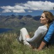 Stock Photo: Couple cuddling looking over lake and hills