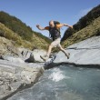 Hiker jumping across river — Stock Photo