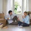 Couple taking a break among moving boxes — Stock Photo