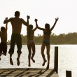Father and children jumping off a pier — Stock Photo #33851973