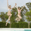 Stock Photo: Women Jumping into Swimming Pool