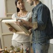 Multiethnic couple looking at canvases — Stock Photo #33853007