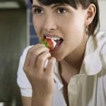Woman biting strawberry — Stock Photo #33859589