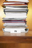 Inbox with stack of paperwork — Stock Photo