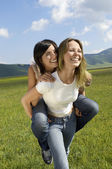 Young woman giving friend piggyback in mountain field half length — Foto de Stock