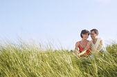 背の高い草の中に座ってカップル — ストック写真