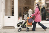 Mother pushing stroller by shop — Stock Photo