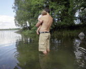 Man Standing in Lake Holding Son — Stock Photo