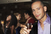 Young man holding drink in bar — Stock Photo