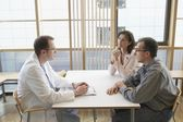 Doctor conversing with a couple — Stock Photo