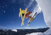 Skiers launching off snow bank — Stock Photo
