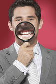 Man holding magnifying glass to smiling — Stock Photo