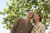 Tourist Couple standing under tree — Stock Photo