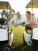 Golfers sitting in golf carts — Stock Photo