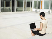 Woman in plaza courtyard using laptop — Stockfoto