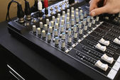 Man adjusting knob on mixing console — Stock Photo