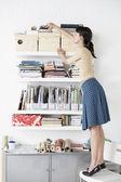Businesswoman reaching for Shelf — Stock Photo