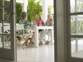People sitting at verandah table — Stock Photo