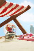 Santa snow globe under deckchair — Stock Photo