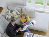 Woman sitting on sofa with financial advisor — Stock Photo