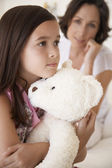 Girl hugging teddy bear — Stockfoto