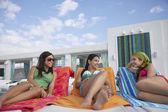 Girls  lying on sunloungers — Stock Photo